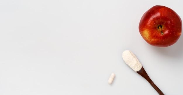 Collageenproteïnepoeder in een plastic maatlepelcapsule op wit, plat leggen.