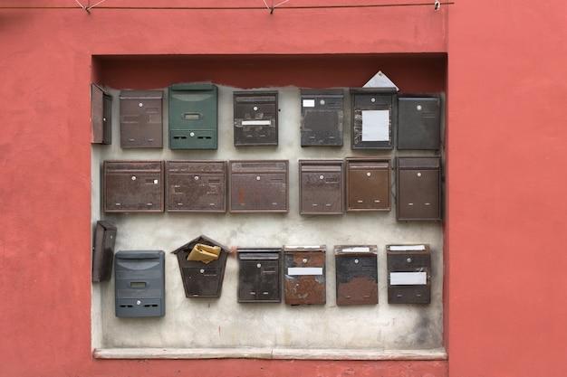 Collectie aan de muur bevestigde brievenbussen in een uitsparing in een roze muur van een flatgebouw of flats in verschillende stijlen en uitvoeringen