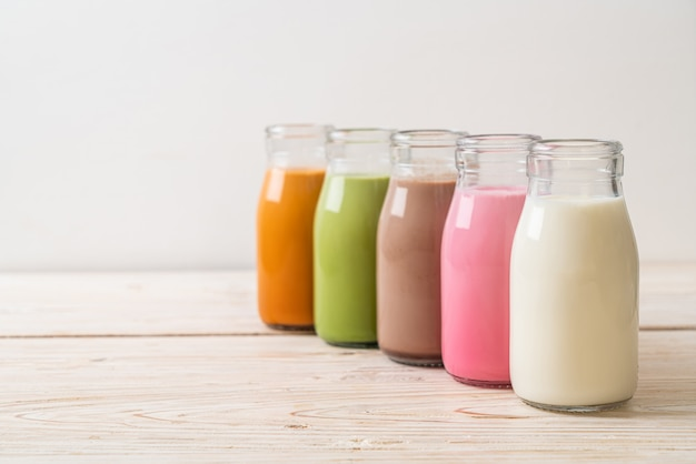 Collectie van drank. thaise melkthee, matcha groene thee latte, koffie, chocolademelk, roze melk en verse melk in fles op houten tafel