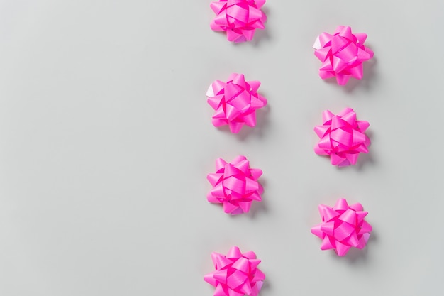 Collectie van roze verjaardagsfeestje objecten voor geschenkdozen. feestelijke samenstelling. lint bogen plat lag op pastel muur. ruimte kopiëren. bogen. wenskaart