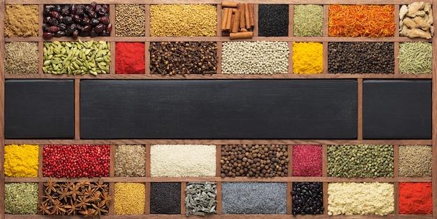 Collectie van specerijen in houten kist, bovenaanzicht. indiase specerijen als achtergrond voor het verpakken met voedsel.