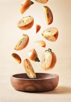 Collectie van vallende persimmon in een houten kom op een beige pastel achtergrond.