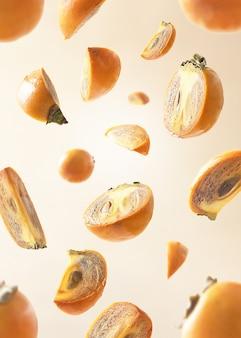 Collectie van vallende persimmon op beige pastel achtergrond.
