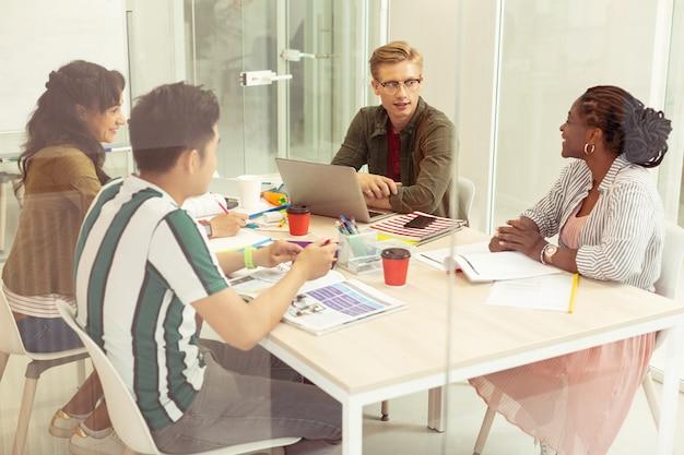 Collectief werk. tevreden internationale studenten die een interessant onderwerp bespreken terwijl ze in hun klas zitten