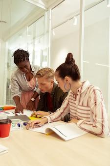 Collectieve discussie. vrolijke donkere lerares buigt haar hoofd terwijl ze naar de nodige tekst wijst