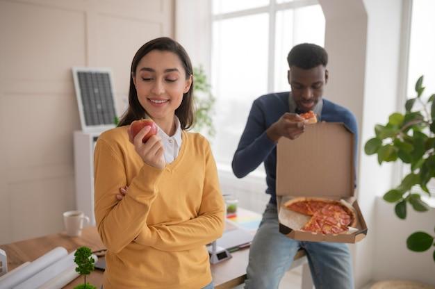 Collega's aan het werk die pizza eten