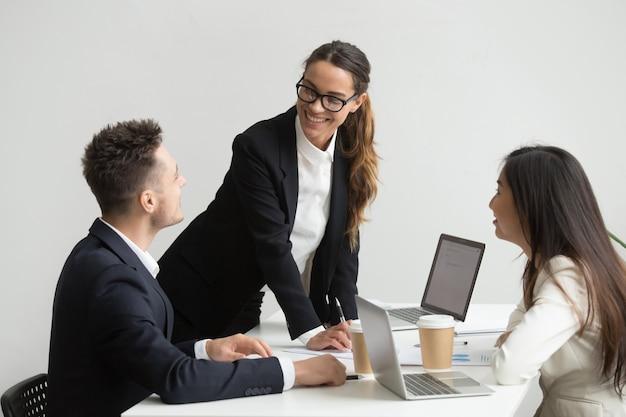 Collega's analyseren van hand-outs en rapporten tijdens vergadering