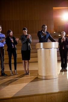 Collega's applaudisseren spreker na presentatie van de conferentie