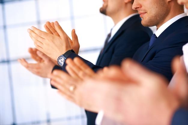 Collega's applaudisseren tijdens een zakelijke bijeenkomst, focus op de handen.