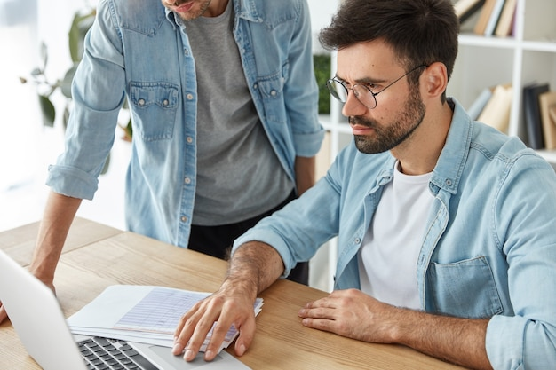 Collega's bespreken nieuwe ideeën om winst te maken, gericht op een laptop, omringd met documenten