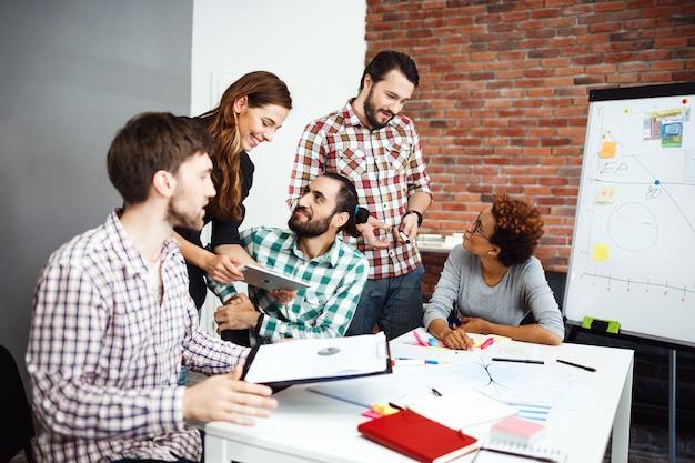 Collega's bespreken nieuwe ideeën op zakelijke bijeenkomst.