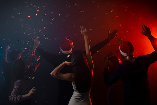 Collega's dansen in confetti op nieuwjaarsfeest