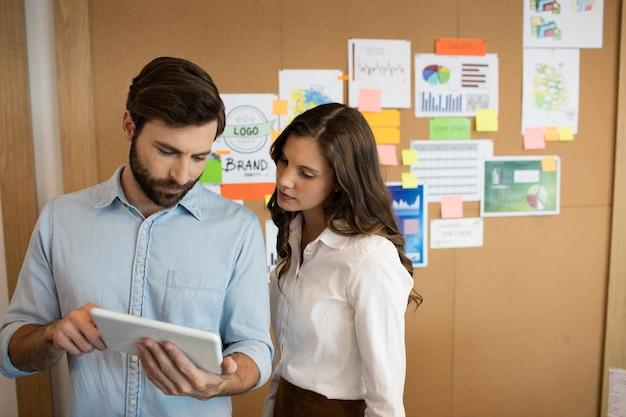 Collega's die aan digitale tablet op kantoor werken