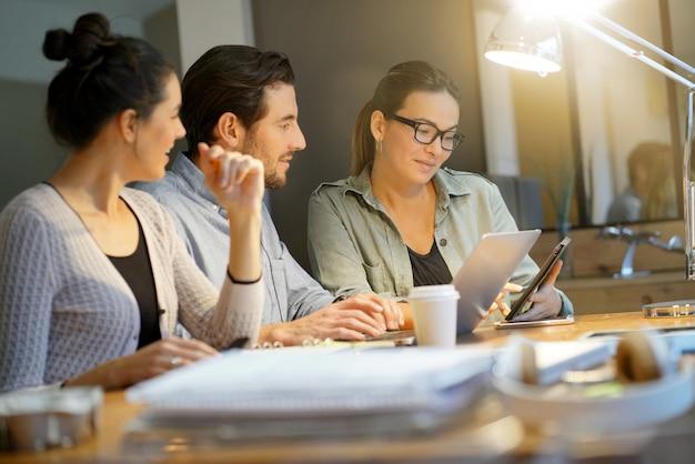 Collega's die bedrijfsideeën in moderne mede het werk ruimte werken