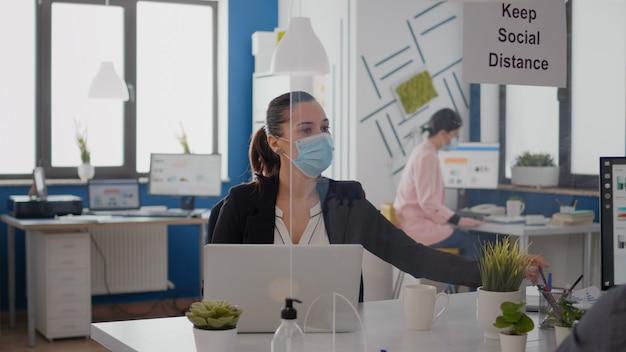 Collega's die een beschermend gezichtsmasker dragen en sociale afstand bewaren om infectie met coronavirus te voorkomen, terwijl ze werken bij de statistieken van het managementbedrijf in een nieuw normaal bedrijfskantoor.
