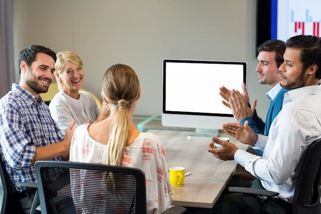 Collega's die een collega applaudisseren tijdens een videoconferentie