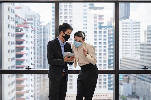 Collega's die gezichtsmasker dragen die het businessplan op tablet raadplegen, aziatische zakenman die met vrolijke manager in modern bureau bespreekt