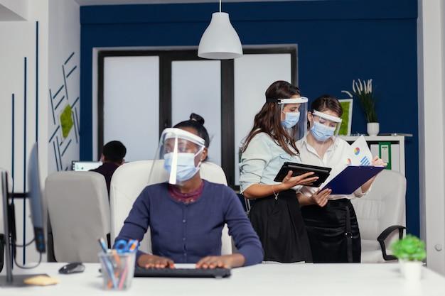 Collega's die goed samenwerken, houden een tablet-pc vast met een gezichtsmasker voor covid19. multi-etnisch zakelijk team dat werkt met respect voor sociale afstand tijdens wereldwijde pandemie met coronavirus.