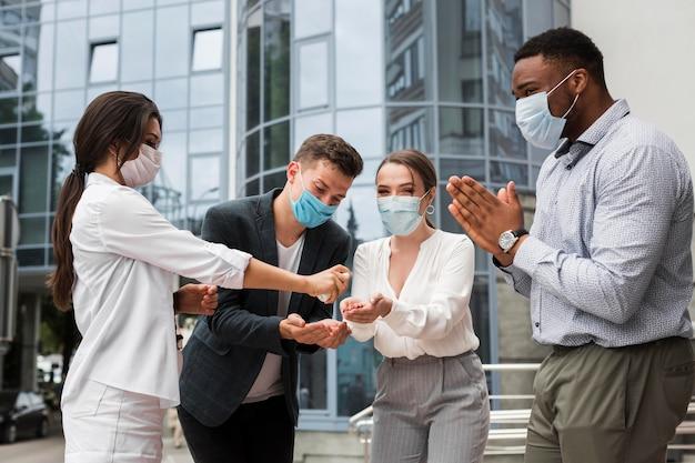Collega's die handen buitenshuis desinfecteren tijdens een pandemie terwijl ze maskers dragen