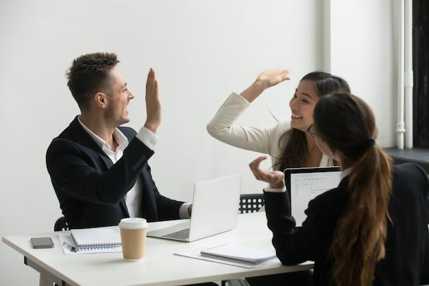 Collega's die hoge vijf geven vieren gedeeld succes