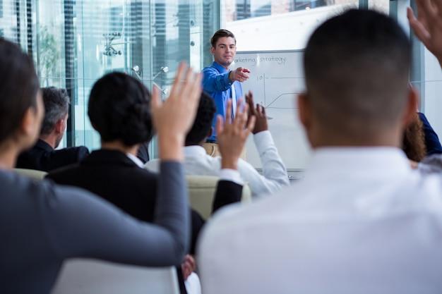 Collega's die hun handen opheffen tijdens de vergadering