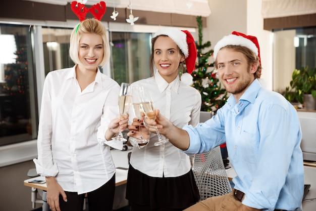 Collega's die kerstmispartij in bureau het drinken champagne het glimlachen vieren.
