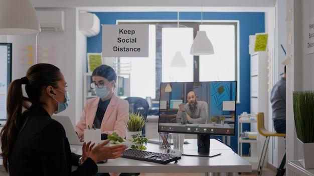 Collega's die medische gezichtsmaskers dragen om infectie met coronavirus te voorkomen terwijl ze in een kantoorbedrijf werken. zakenvrouw in gesprek met haar team tijdens online communicatievergadering