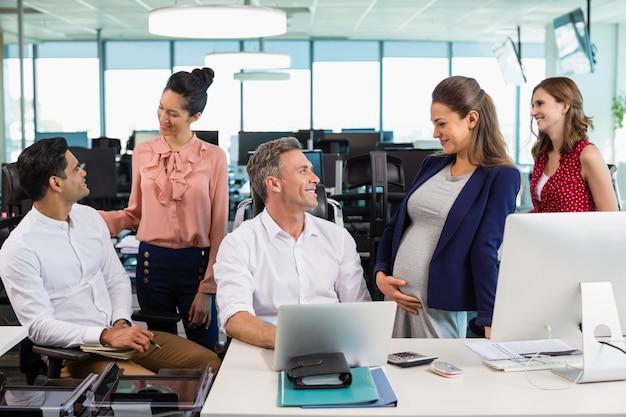 Collega's die met elkaar omgaan bij het bureau op kantoor