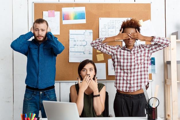Collega's die mond, ogen en oren sluiten met handen in functie zie-hoor-spreek geen kwaadaardige variatie.