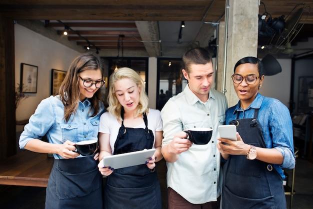 Collega's die op digitale apparaten bij een koffiewinkel spelen