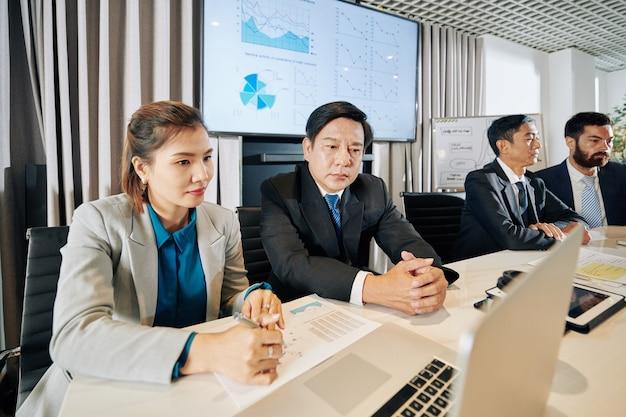 Collega's die presentatie op laptop bekijken en gegevens in rapporten bespreken