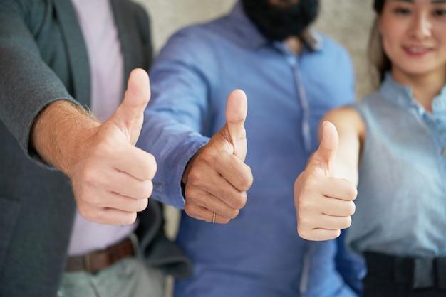 Collega's die samen in bureau stellen en duimen tot camera tonen