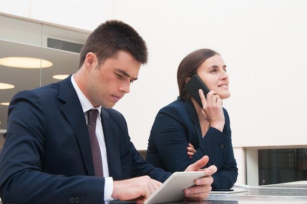 Collega's die tablet gebruiken en telefoon bij bureau in openlucht roepen