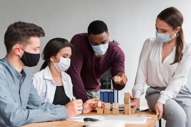 Collega's die tijdens een pandemie op kantoor vergaderen met medische maskers op