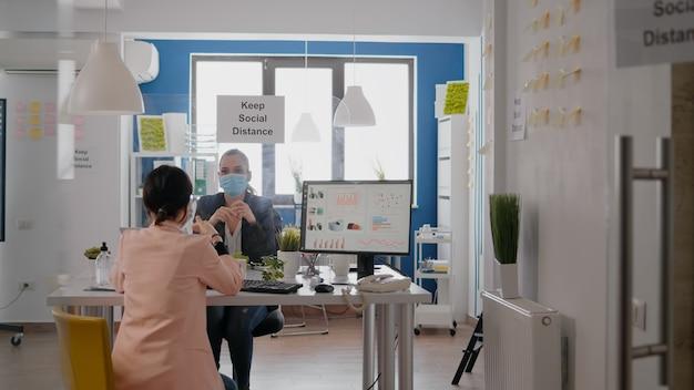Collega's die werken op zakelijke bijeenkomsten die een beschermend gezichtsmasker dragen met respect voor sociale afstand om covid19-infectie te voorkomen, terwijl ze aan een tafel zitten in een startend kantoorbedrijf.