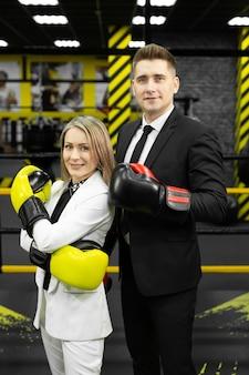 Collega's, een man en een vrouw in pakken en bokshandschoenen in de ring.