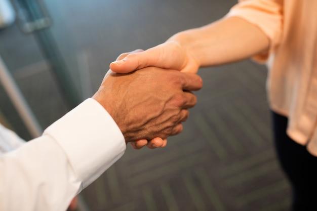 Collega's handen schudden in kantoor