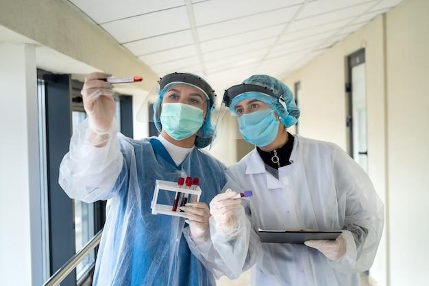 Collega's houden reageerbuisjes met bloed vast met een positief resultaat voor coronavirusinfectie. covid-19 thema