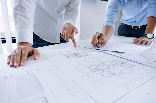 Collega's interieurontwerper corporate achievement planning ontwerp op blauwdruk teamwork concept met kompassen.