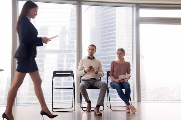 Collega's kijken naar ingehuurde gepromote blije collega met haat jaloezie