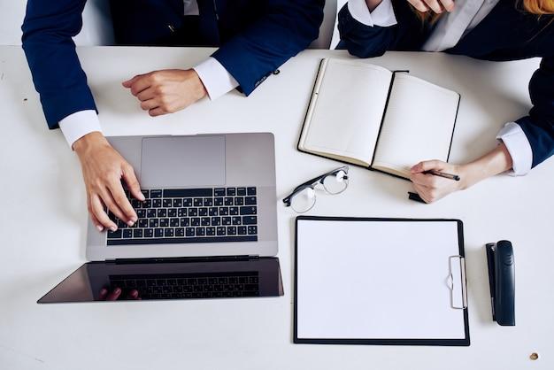 Collega's laptop en documenten op tafel technologie