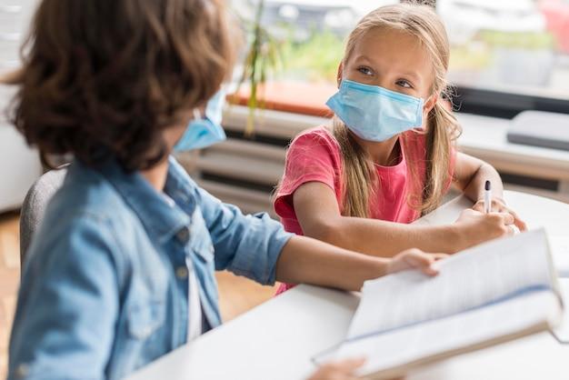 Collega's maken hun huiswerk terwijl ze een medisch masker dragen