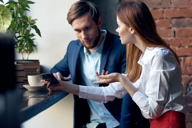 Collega's man en vrouw zitten in een café met telefonische communicatie