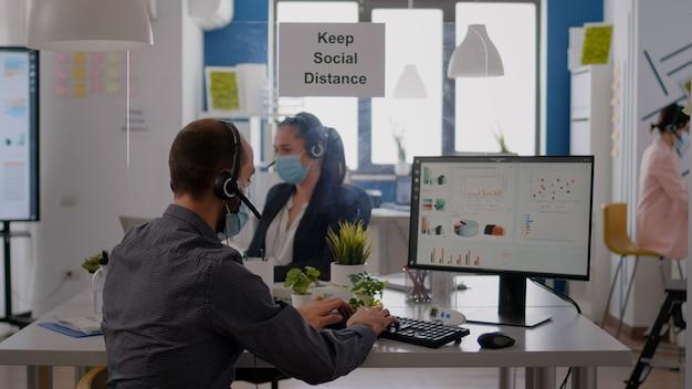 Collega's met koptelefoon die in de microfoon praten terwijl ze werken bij financiële statistieken in het bedrijfskantoor. teamwerkers die beschermende gezichtsmaskers dragen om infectie met coronavirus te voorkomen