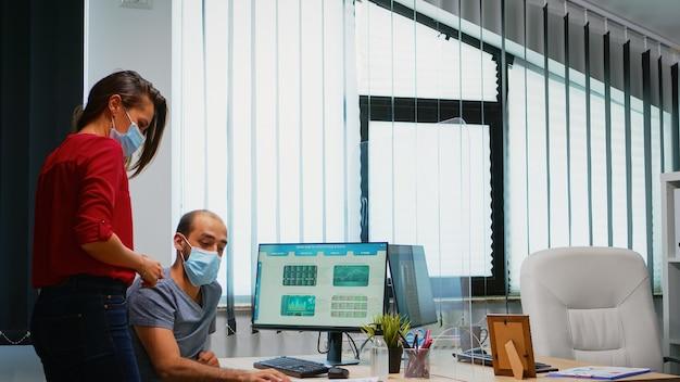 Collega's met maskers die afbeeldingen bespreken die in een nieuwe normale kantoorruimte zitten. collega's die aan het werk zijn, wijzend op het bureaublad met respect voor sociale afstand tegen het covid-virus met behulp van plexiglas.