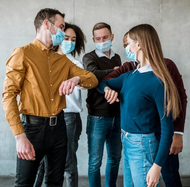Collega's met medische maskers doen de ellebooggroet tijdens een vergadering