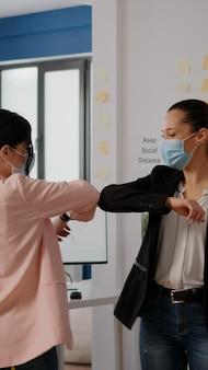 Collega's met mondkapjes begroeten elkaar met elleboog