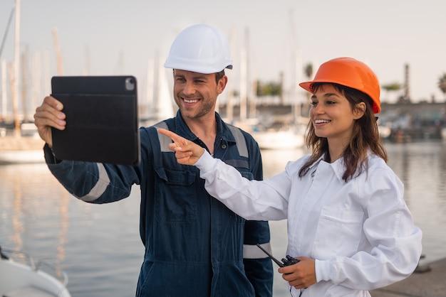 Collega's met tablet die in haven werken