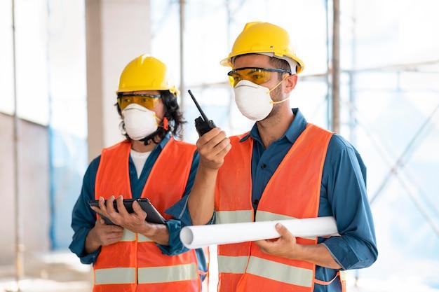 Collega's met veiligheidsuitrusting die met blauwdrukken werken