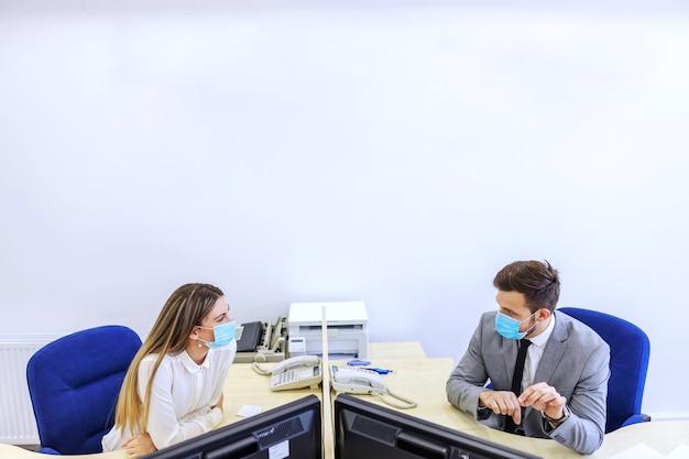 Collega's op kantoor en het corona virus. een man en een vrouw zitten aan een bureau op kantoor en praten door een beschermende barrière. ze dragen allebei beschermende gezichtsmaskers en praten over werk